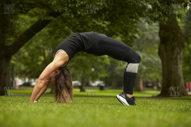 A woman does a back bend in the grass of the Boston Public Garden.