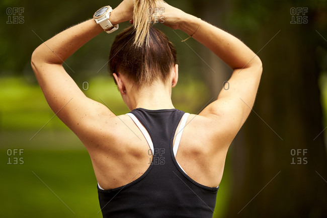 A woman tying her hair back before a run.