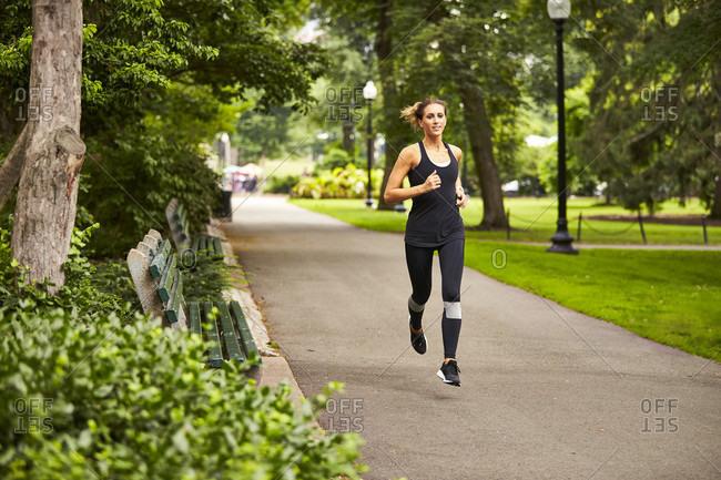 A woman running along a path in the Boston Public Gardens.
