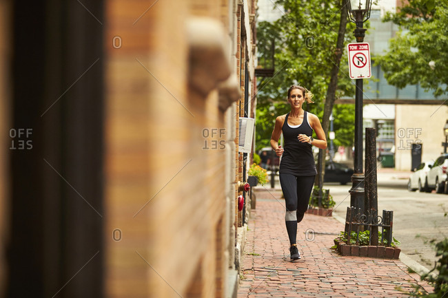 A woman running down a city street in Boston.