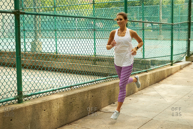 A woman runs along a colorful fence in the city.