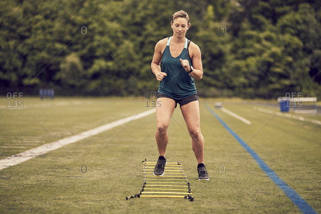 Front view of female athlete doing agility ladder exercises at athletic field, Lincoln, Massachusetts, USA