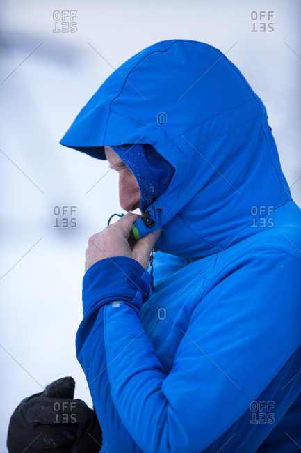 Side view of backcountry skier adjusting hood of blue jacket, Clinton, Montana, USA