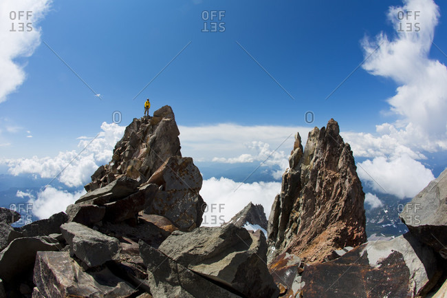 Man standing atop large jagged boulder while hiking, Lakes District, Chile