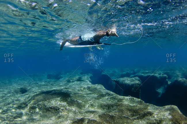 Underwater view of surfer above reef at Pipeline, on North Shore of Oahu, Hawaii, USA