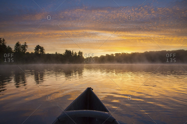 First person view of canoeist paddling through calm waters on Tooley Pond at sunrise, Tooley Pond, New York, USA
