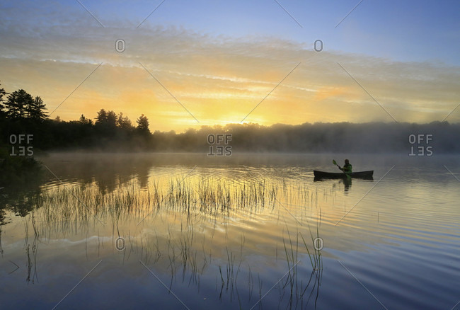 Lone canoeist paddling through calm waters on Tooley Pond at sunrise, Tooley Pond, New York, USA