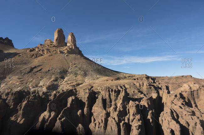 Rock formation and barren hills against sky, Chubut, Argentina