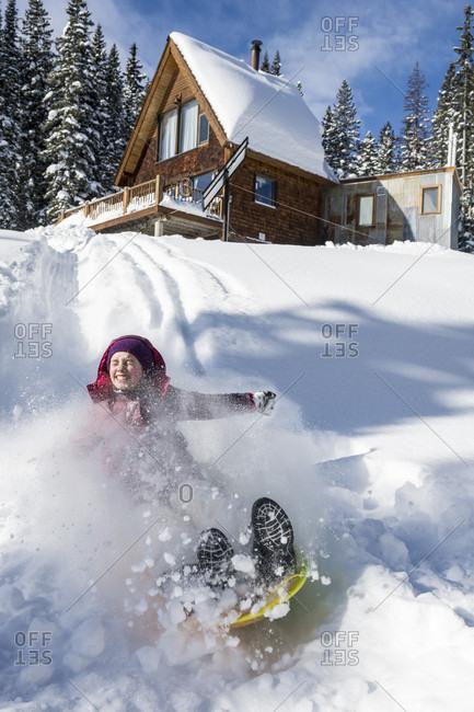 Young girl sledding in powder snow below mountain cabin near Molas Pass, Silverton, Colorado, USA