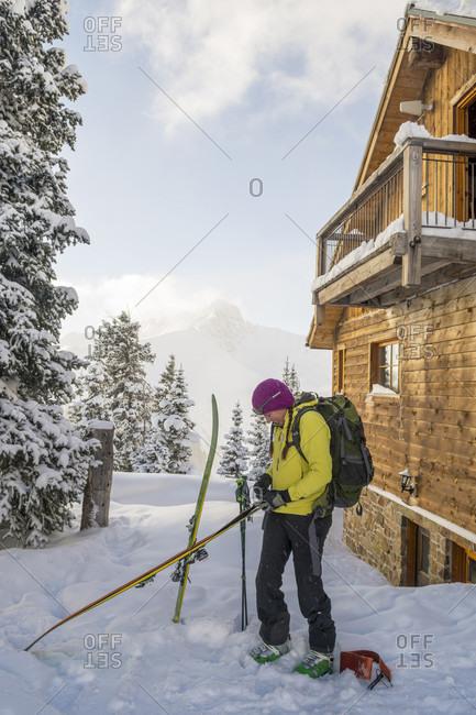 Female skier preparing for backcountry skiing, San Juan National Forest, Silverton, Colorado, USA