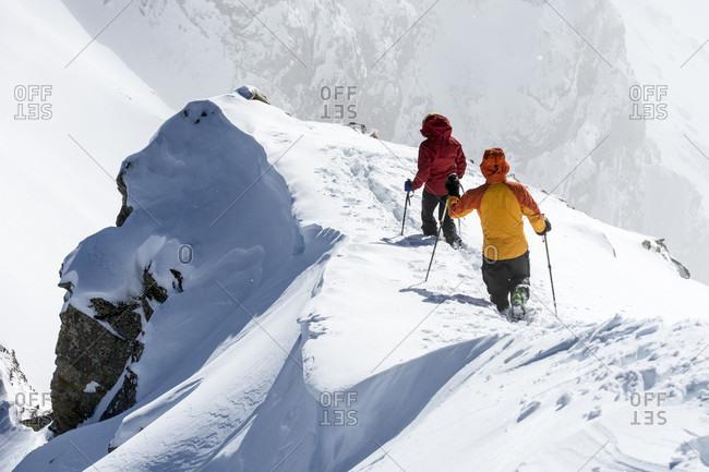 Man and woman hiking snowy ridge, San Juan National Forest, Silverton, Colorado, USA