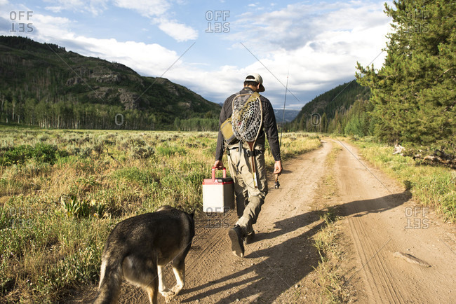Fisherman walking on dirt road with pet dog, Steamboat Springs, Colorado, USA