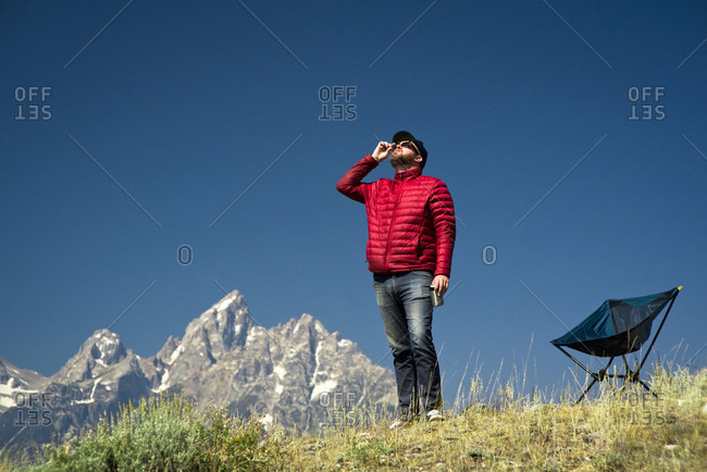 A guy standing in front of the Teton Mountains stares up at sun waiting for a total eclipse in Jackson Hole Wyoming.