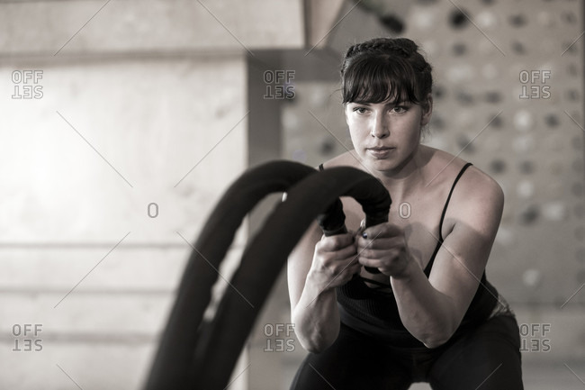 A strong female trains with ropes in the fitness gym