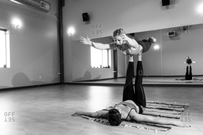 Two fit females practice acro yoga together inside a yoga studio