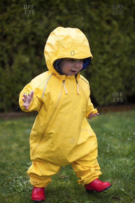 Portrait of smiling and running baby in yellow rain suit, Surrey, Canada
