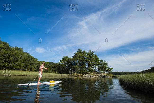 Sky over man paddle boarding along grassy shoreline of Brave Boat Harbor, Kittery, Maine, USA
