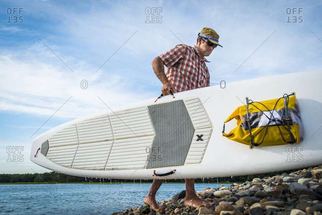 Paddle boarder carrying surfboard on rocky shore, Kittery, Maine, USA