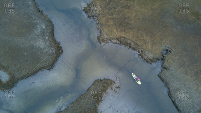 Aerial view of paddle boarder surfing in Scarborough Marsh, Maine, USA