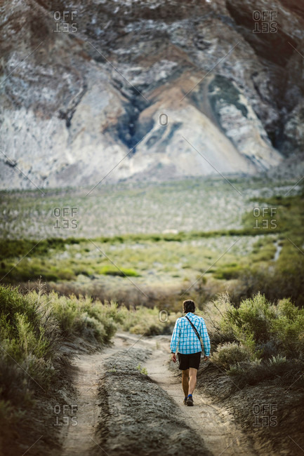 Rear view of lone woman walking on dirt road in desert in Saline Valley, Death Valley National Park, California, USA
