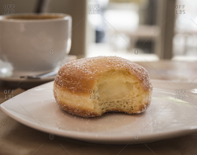 Vanilla cream doughnut with missing bite on white plate and coffee in background, Brooklyn, New York City, USA