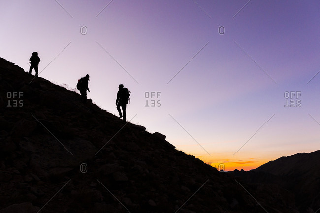 Silhouettes of three hikers walking up hill against purple sky at dusk, Walden, Colorado, USA
