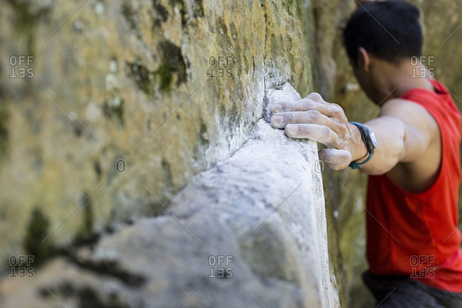Man climbing rock wall with chalk-covered hands, Wisconsin, USA
