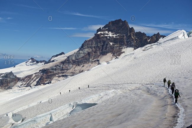 Group of mountain climbers ascending through crevasse field to Camp Schurman on Mount Rainier, Mount Rainier National Park, Washington State, USA