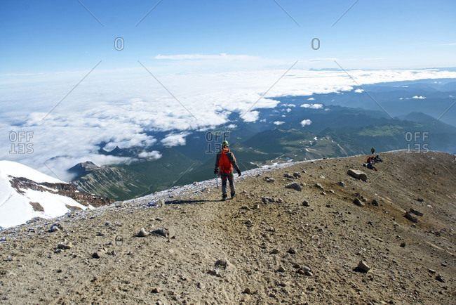 Rear view of mountain climber on Liberty Cap at summit of Mount Rainier, Mount Rainier National Park, Washington State, USA