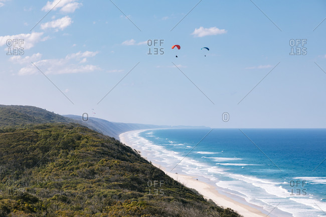 Two distant paragliders flying above Laguna Bay and Great Sandy National Park, Noosa Heads, Queensland, Australia