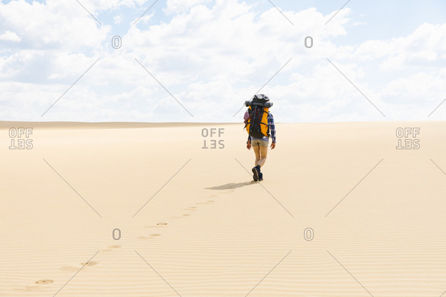 Rear view of woman hiking on sandy beach in Great Sandy National Park, Noosa Heads, Queensland, Australia