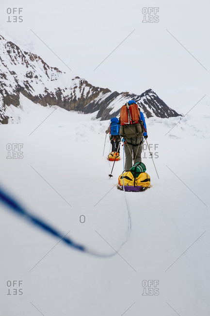 Climbers tow sleds on the lower Kahiltna Glacier in the Alaska Range of mountains, Denali National Park and Preserve.