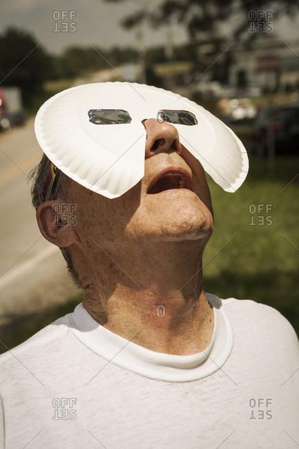 Older man views eclipse through homemade glasses