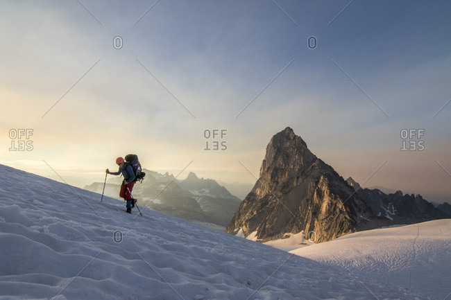 Side view of mountain climber traversing Vowell Glacier at sunset, Bugaboo Mountains, British Columbia, Canada