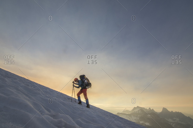 Side view of mountain climber traversing glacier at sunset, Bugaboo Mountains, British Columbia, Canada