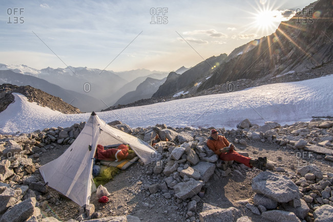 Resting mountain climber sitting near tent, East Creek Basin Bivy, Bugaboo Mountains, British Columbia, Canada