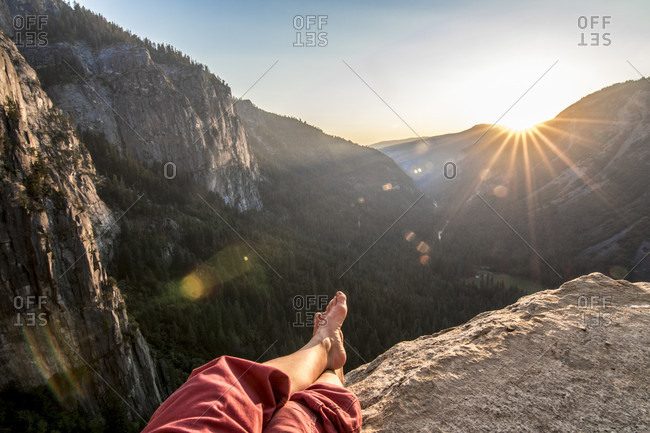 Legs of person resting at Dano Ledge at sunset, Yosemite National Park, California, USA