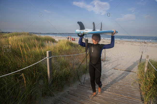 A ten-year-old boy carries his board after surfing at Nahant Beach in Nahant, Massachusetts.