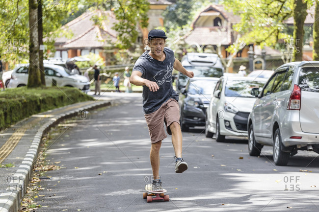 Front view of man with skateboard on street, Bedugul, Bali, Indonesia