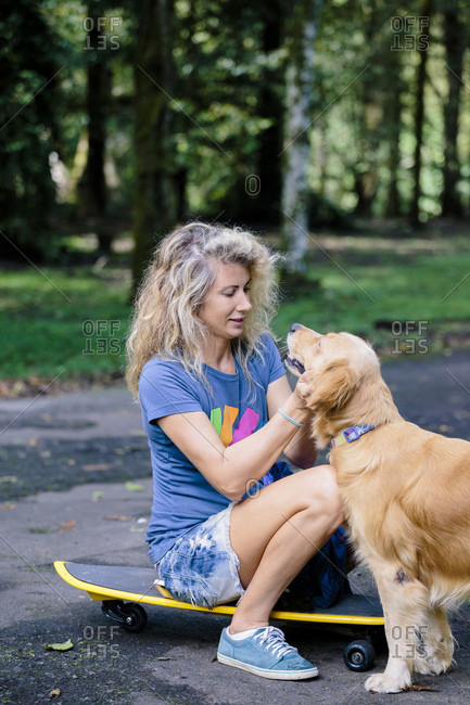 Photograph of blonde-haired woman with dog sitting on skateboard, Bedugul, Bali, Indonesia