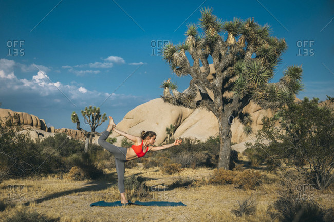 A young woman  in yoga dancer pose, Joshua Tree National Park