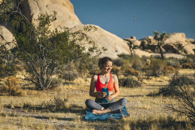 A young woman hydrates after doing yoga in Joshua Tree National Park