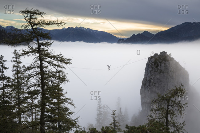 Side view of person walking on high line in clouds above Traunsee lake, Upper Austria, Austria