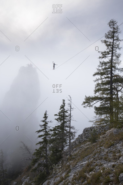 Low angle view of person walking on high line in clouds above Traunsee lake, Upper Austria, Austria