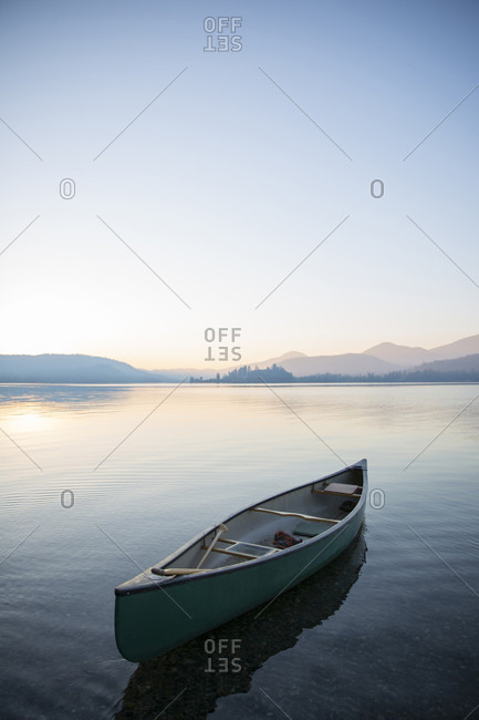 Lone empty canoe floating on Lake Pend Oreille under clear sky at sunset, Sandpoint, Idaho, USA