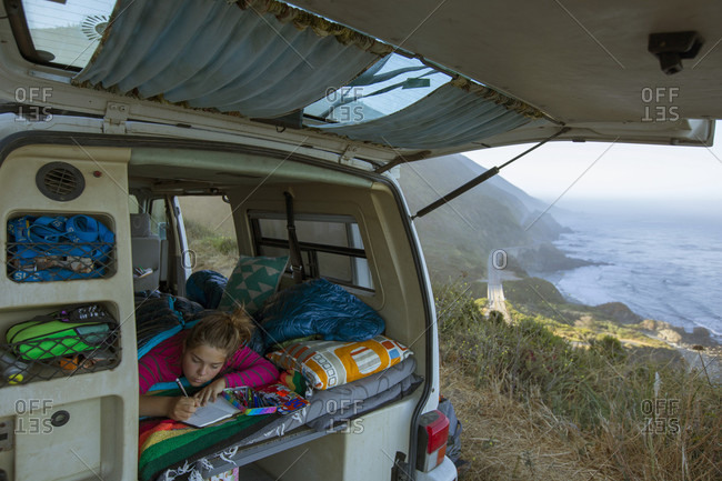 Girl busy writing in diary in van while on road trip along Big Sur coastline, California, USA