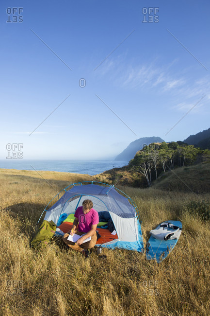 Sky over man sitting inside pitched tent and writing in journal, California, USA