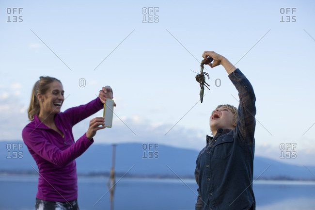 Adult woman laughing while photographing boy pretending to eat crayfish, Sandpoint, Idaho, USA