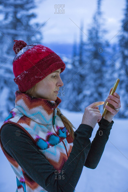 Side view of woman in winter clothing texting on smartphone outdoors in winter, Sandpoint, Idaho, USA