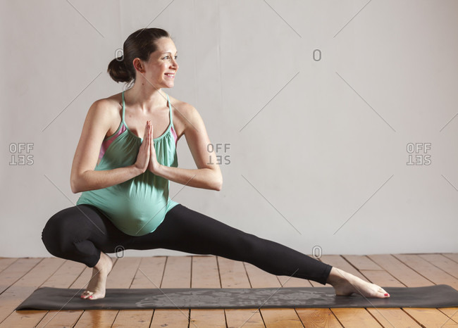 Pregnant women doing yoga pose side lunge and stretching with hands in prayer, Boston, Massachusetts, USA